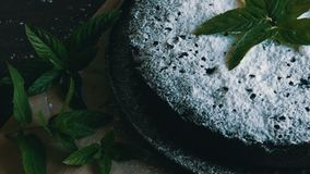 Stylish homemade baked chocolate brownie cake generously powdered with an icing sugar next to fresh mint leaves. Stylish homemade baked chocolate brownie cake stock footage