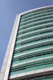 Stylish Hospital in Central London. Tall sky rise building in London with green windows on a sunny day with blue sky Royalty Free Stock Image