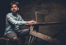 Stylish  Indian male working with laptop. Stylish bearded Indian male working with laptop Royalty Free Stock Photos
