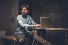 Stylish  Indian male working with laptop. Stylish bearded Indian male working with laptop Royalty Free Stock Photography