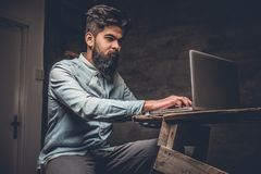Stylish  Indian male working with laptop. Stylish bearded Indian male working with laptop Royalty Free Stock Image