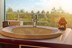 Stylish indoor setting - bathroom sink with a garden view at sun Stock Photos