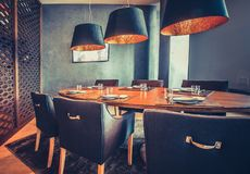 Orange table, blue chairs, lamps. Restaurant decor. royalty free stock image