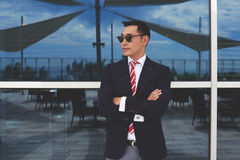 Stylish intelligent asian men in sunglasses standing against glassy window with city reflection. Portrait of a young confident managing director with arms stock photography