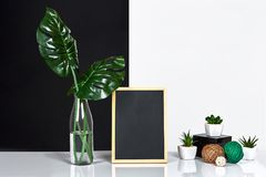 The stylish interior with mock up poster frame, leaves in glass bottle on table with black and white wall on background. The minimalism concept of space. Copy royalty free stock photos
