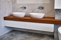 Stylish interior of modern bathroom with teak tabletop and marble walls. Ceramic round sinks placed on teak tabletop in luxury water closet with gray and white stock photos