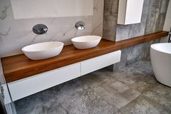 Stylish interior of modern bathroom with teak tabletop and marble walls. Ceramic round sinks placed on teak tabletop in luxury water closet with gray and white stock photography