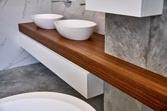 Stylish interior of modern bathroom with teak tabletop and marble walls. Ceramic round sinks placed on teak tabletop in luxury water closet with gray and white royalty free stock photo