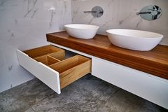 Stylish interior of modern bathroom with teak tabletop and marble walls. Ceramic round sinks placed on teak tabletop in luxury water closet with gray and white stock photo