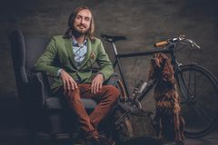 A man with dog and bicycle. A stylish Irland hipster man posing with single speed bicycle and Irish setter dog Royalty Free Stock Images