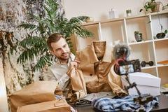 Stylish jacket. Positive male fashion blogger holding beige jacket while making new video for his fashion blog. Youtube. Instagram. Social media stock photos
