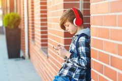 Stylish kid boy with headphones using phone at city street. Young boy plays online game at smartphone. Preteen boy listens to the. Music on smart phone royalty free stock photo