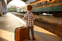 Stylish kid with luggage on train station. Back view of trendy boy posing on railway station with suitcase Stock Photography