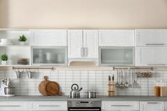 Stylish kitchen interior with new furniture. And utensils stock photography