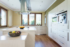 Stylish kitchen with island. Spacious stylish kitchen with wooden parquet and bright units. In the middle big island Stock Photography