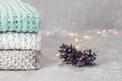 Stylish knitted pastel colored sweaters folded in stack with pine cones on velvety fabric background. Close up, copy stock images