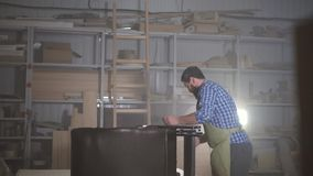 Man with a beard in a shirt in the workshop. Stylish kraftman in a dark workshop working with furniture stock video