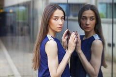 Stylish lady in blue dress posing near mirrored wall Stock Image