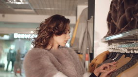 Stylish lady choosing the fur coats in boutique stock video
