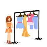 Stylish lady with clothes in a rack. Creative stylish fashionable girl with colorful dresses rack on beige background Royalty Free Stock Photography