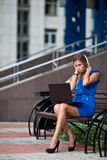 Stylish lady with laptop sitting on a bench Stock Images