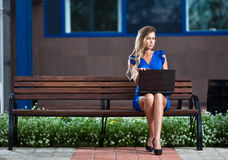 Stylish lady with laptop sitting on a bench Royalty Free Stock Photo