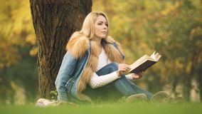 Stylish lady reading adventure book in central park, sitting under tree, autumn stock video