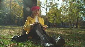 Stylish lady is reading book in the park. Blond bright dressed lady is reading book at the park sitting under the tree. Spending time outdoor in modern city stock footage