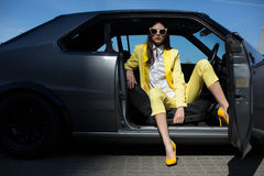 Stylish lady sitting in the car with opened door. Fashion girl driving a car in a suit. Royalty Free Stock Photo