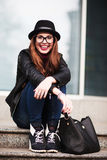 The stylish laughing happy  city girl in sunglasses  sits on ste Stock Photo