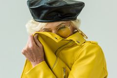 Stylish laughing senior woman in yellow leather jacket and yellow sunglasses,. Isolated on grey royalty free stock photography