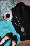 Stylish layout of clothes and accessories. Turquoise pants, evening top, black shoes, rosary and a cup of coffee Stock Images