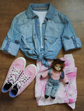 Stylish layout of clothes, top view. Jeans shirt, pink sneakers, summer skirt and a doll-cat Royalty Free Stock Photos