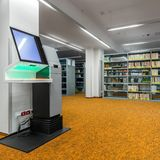 Library interior with modern technology. Stylish library interior with orange flooring and modern device for lending books royalty free stock photos