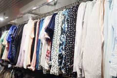 Stylish light-colored blouses on hangers. Elegant light blouses hanging on metal rack in modern clothes shop royalty free stock photos