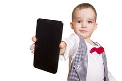 Stylish little boy in checkered suit and bow tie shows a mobile Stock Image
