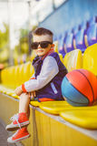 Stylish  little boy posing at basketball court. Rapper attitude rap singer hip Hop Dancer performing. Stylish  little boy posing at basketball court Royalty Free Stock Photos