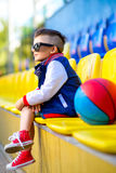 Stylish  little boy posing at basketball court. Rapper attitude rap singer hip Hop Dancer performing. Stylish  little boy posing at basketball court Stock Image