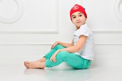 Stylish little boy in a red hat and jeans on a white background in the studio. Fashionable children.  royalty free stock photos