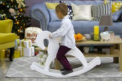 Stylish little boy ride on a rocking horse in room with modern desing. Christmas stock image
