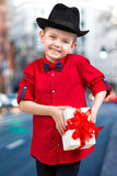 Stylish little boy in a shirt and hat gives gift surprise.Fashionable dandy. Stylish boy in a shirt and hat gives gift surprise royalty free stock photography