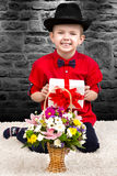 Stylish little boy in a shirt and hat with a surprise gift and a bouquet of flowers.Trendy dandy. Stylish little boy in a hat.Gifts,surprises and flowers royalty free stock images