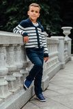 Stylish little boy in sunglasses and fashionable clothes . Children`s fashion. Stylish rich little boy in fashionable clothes . Leaned on Granite-stone handrails Royalty Free Stock Images