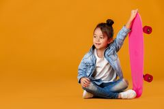 e78e6920f442 Stylish little child girl with skateboard in denim on orange background.  Stylish little child girl