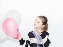 Stylish little concentrated girl looking at pink ballon Royalty Free Stock Photography