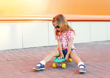 Stylish little girl child with skateboard wearing sunglasses in city Royalty Free Stock Image