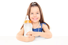 Stylish little girl holding huge baby bottle seated at table Stock Photos