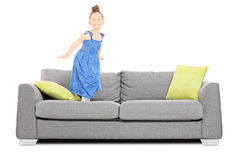 Stylish little girl jumping on couch Royalty Free Stock Image