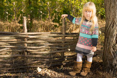 Stylish little girl next to a rustic wooden fence Stock Images