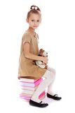 Stylish little girl sitting on a pile of books Royalty Free Stock Photos